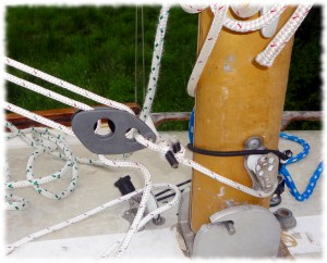 The vang attaches to the mast with a line looped around the mast (and run though an eye strap on the forward edge of the mast)