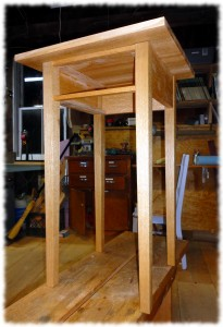 Nightstand after glue-up. The top is just resting on the base. An initial coat of shellac has been applied to the table