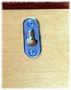A simple keyhole hanger flush mounted on the back.