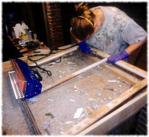 Susanna working on a window sash.