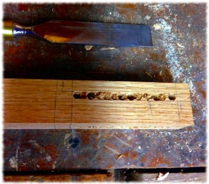 The leg after the the drill press. The remainder of the wood in the mortise will be removed by chisel.