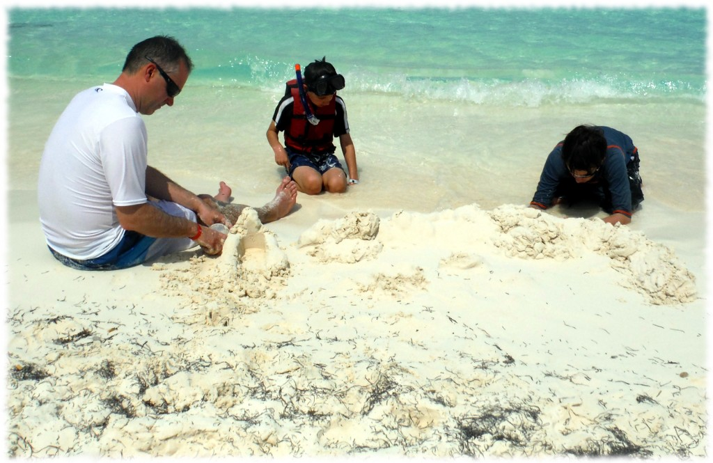 Making sand castles in the white sand on the beach in Cancun.