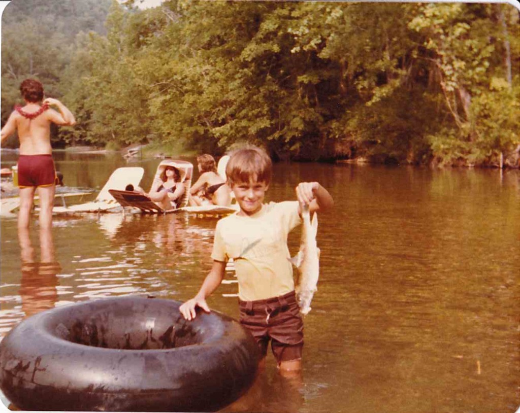 """Chuck Curtis and his """"catch."""" Current River canoe trip, 1980"""