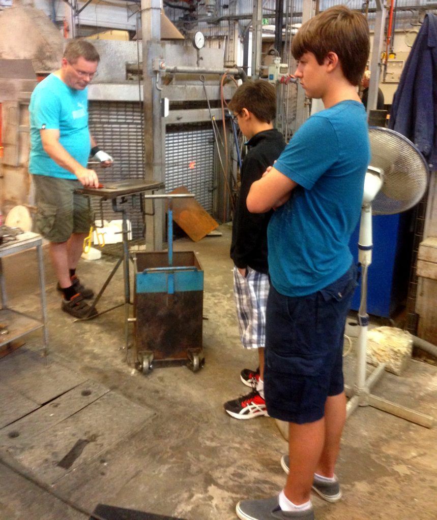 Will and Ben watching the glass blowers work at Kosta, Sweden.