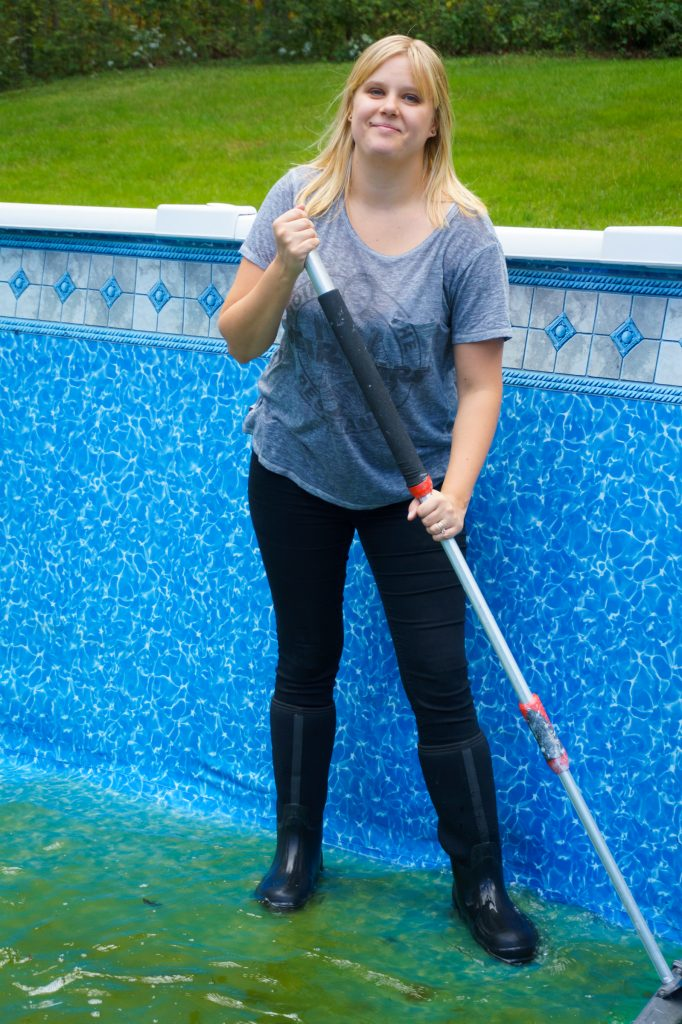 Susanna working on cleaning out water from the old swimming pool prior to taking it down.